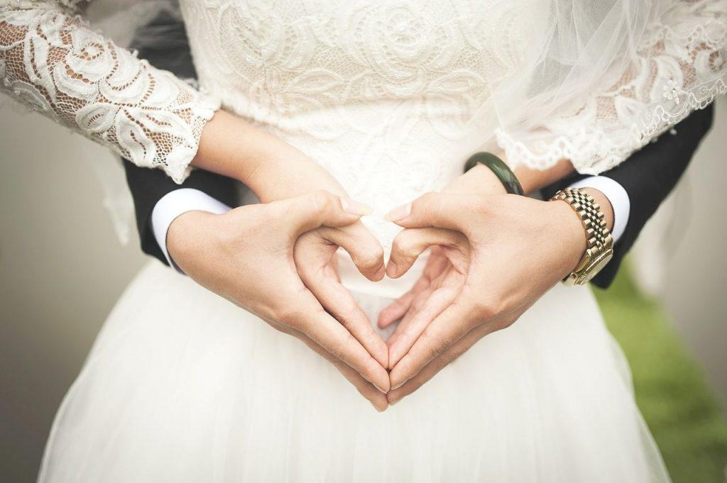 para nowożeńców ich dłonie ułożone w kształt serc