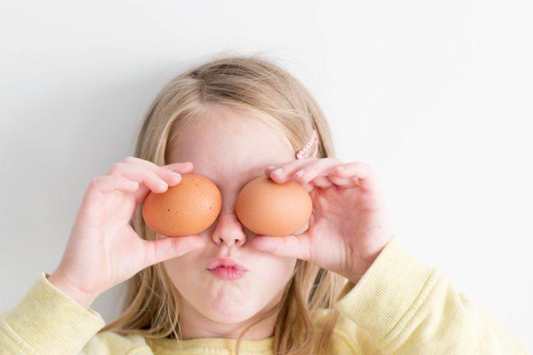 dziewczynka zasłaniająca oczy kurzymi jajkami