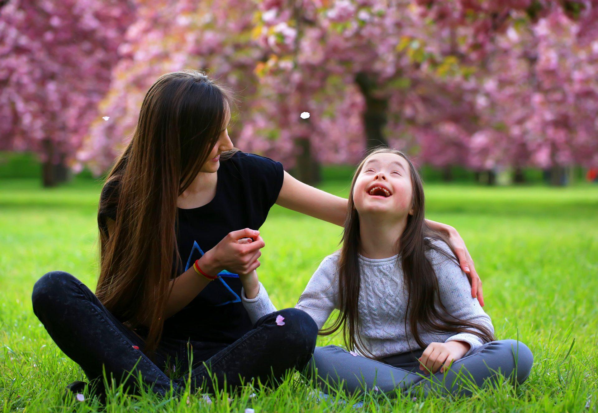 NA zdjęciu osoba dorosła i dziecko z zespołem Downa