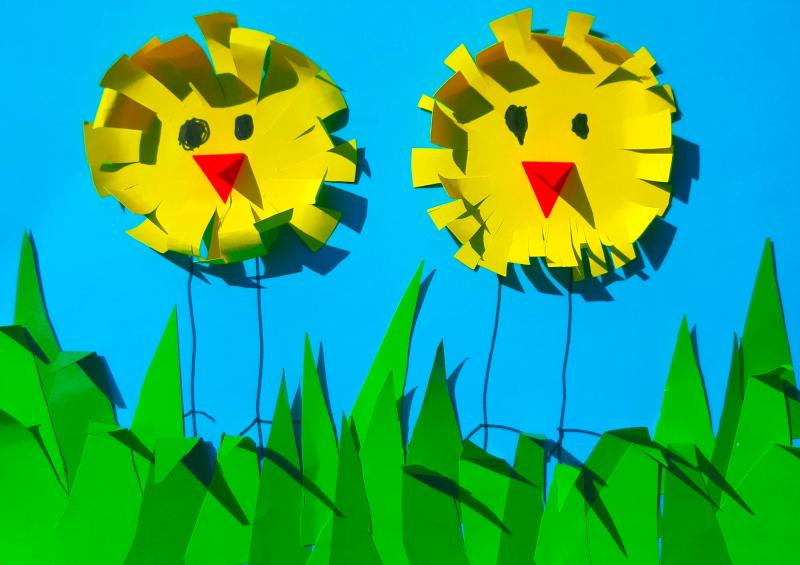 Kartka świąteczna na niej dwa żółte kurczaczki wycięte z żółtego papieru w kształcie kółek w zielonej trawie